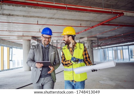 Smiling architect in suit with helmet on head talking to contractor while standing in building in construction process. Architect holding tablet.