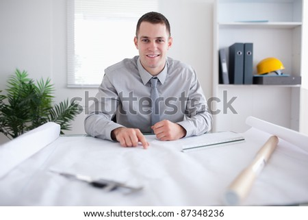 Smiling architect pointing at a plan - stock photo