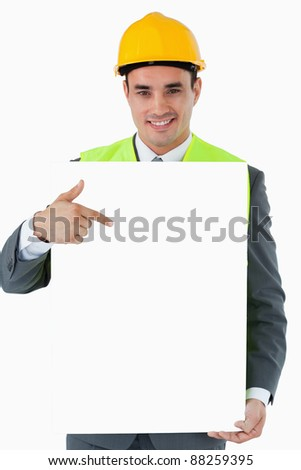 Smiling architect pointing on sign in his hands against a white background