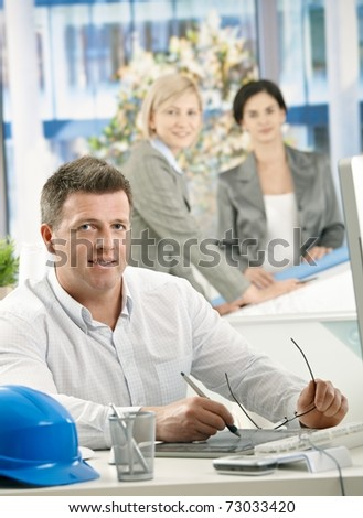 Smiling architect sitting at work, using drawing pad, designers in background.?