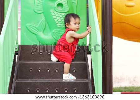 Smiling Asian baby child girl aged of 1 year old practice to crawling and walking with a stair way at the playground. She wearing a red clothes. Development of baby concept.