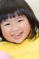 Smiling Asian baby, closeup portrait of young girl face.