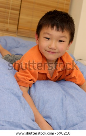 smiling asian boy on bed