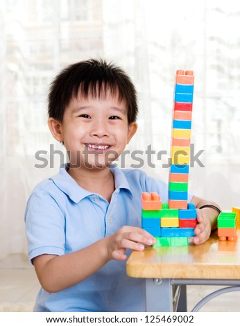 smiling asian boy playing with building blocks