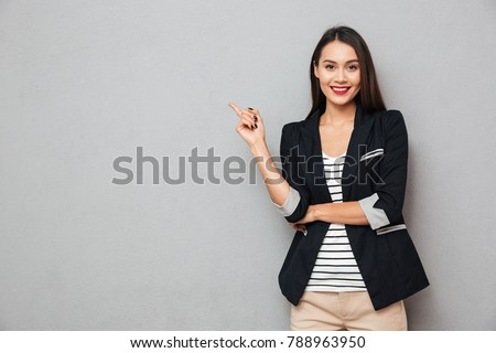 Smiling asian business woman pointing up and looking at the camera over gray background