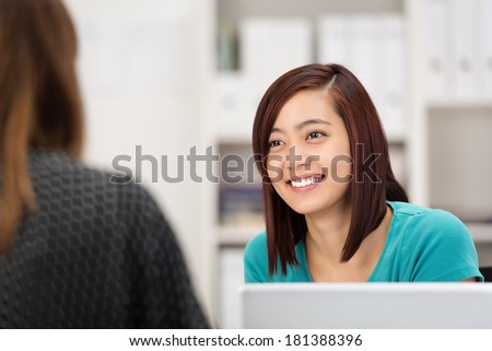 Smiling Asian businesswoman chatting to a female colleague as she sits at her desk in the office