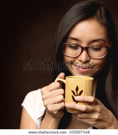 Smiling Asian / Caucasian Woman With Glasses. Girl holding and smelling a Mug of Coffee / Milk / Tea / Hot Chocolate. Brown Background. With Copy Space for Text.