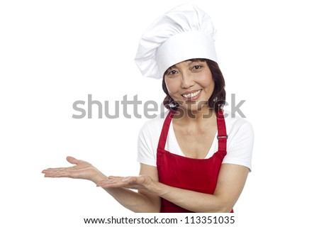 Smiling asian chef gesturing guests to take their seats. All on white background
