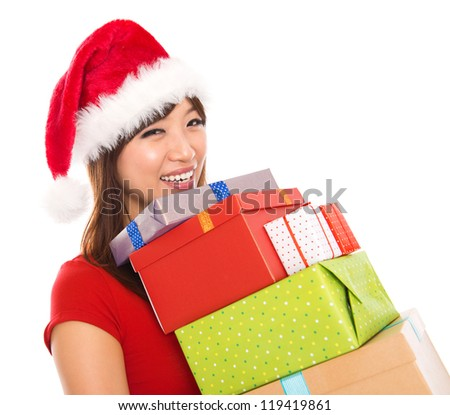 Smiling Asian Christmas woman holding gifts wearing Santa hat, isolated on white background.