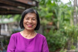 Smiling Asian elderly woman looking at camera standing outside at home