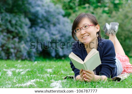 Smiling asian girl reading a book at the park - stock photo