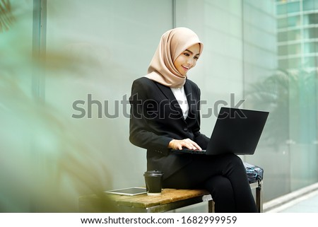 Smiling Asian girl student professional employee typing on laptop sit at outdoor park, happy woman studying e learning online software using technology app for work education concept