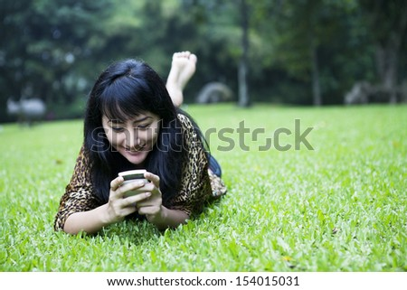 Smiling asian girl using a mobile phone, lying on the grass