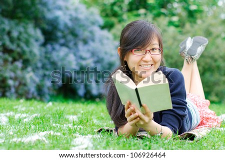 Smiling asian girl with a book at the park