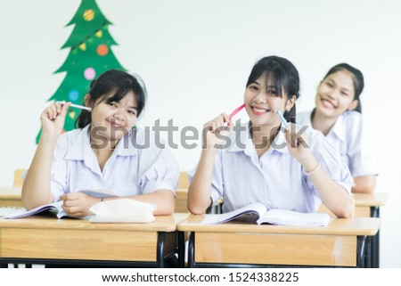 Smiling Asian girls students applaud with school uniform in highschool for activities learning play learn on desk in classroom with happiness, education activity in college, educational active learner