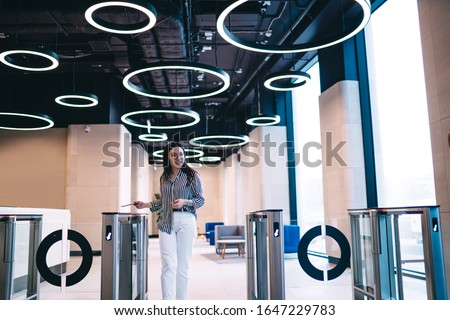 Smiling Asian joyful trendy female employee using office pass for going through electronic gate in corporate design hall looking away Сток-фото ©