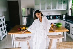 Smiling Asian lady in white clothing with toothy smile leaning on counter and looking at camera while spending time in Bali