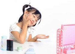 smiling asian little girl is applying make up baby powder her face isolated in white background