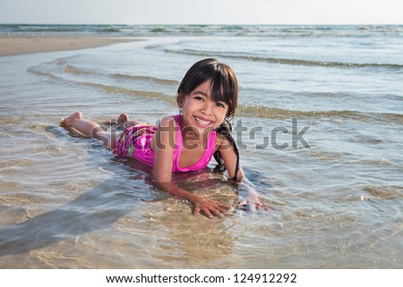 Smiling asian little girl playing on beach