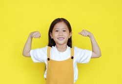 Smiling asian little girl showing his muscle with looking camera isolated on yellow background.