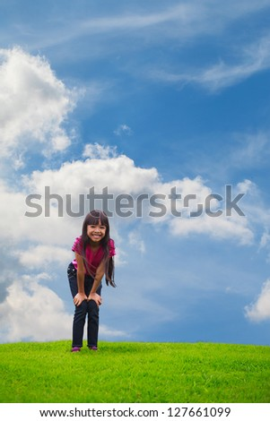 Smiling asian little girl standing on green grass, Outdoor Portrait