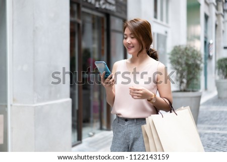 Smiling Asian Thai girl holding gift in shopping bags She Compares prices on mobile smartphones looking for clothes in a dress shop  - Concepts of relaxing lifestyle,shopping online technology in city Stock foto ©