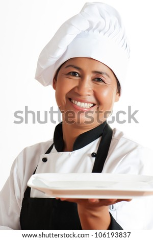Smiling asian woman as restaurant chef with a plate in the hand