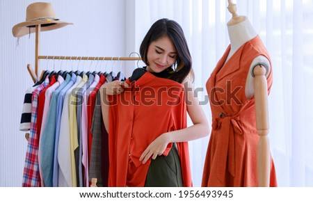 Smiling Asian woman Choose and try on clothe orange color in the Tailor shop. Fashion designer standing in clothing In order to repair, service for customers. Concept Profession Dressmaker designer Foto stock ©