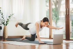 Smiling Asian woman doing one arm one leg plank to exercise core muscle online workout class from laptop at home in living room. Self isolation and workout at home during COVID-19.