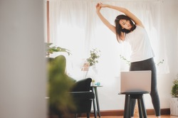 Smiling Asian woman doing stretching along with online class from laptop at home in living room. Self isolation and workout at home.
