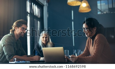 Smiling asian woman giving presenting over laptop to colleagues in meeting room. Happy business professionals meeting in office.