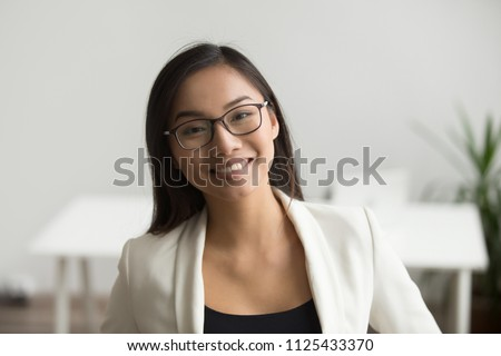 Smiling asian woman in glasses for vision correction looking at camera, happy friendly chinese student or employee posing in office, millennial japanese woman professional head shot portrait #1125433370