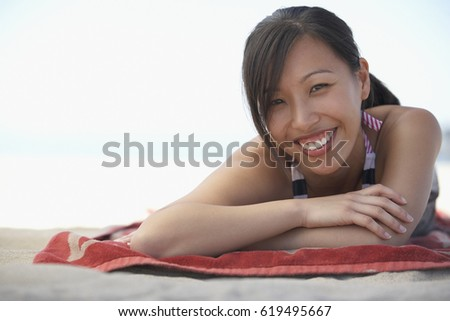 smiling asian woman laying on...