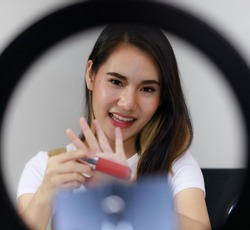 Smiling Asian Woman Live Broadcast Selling make-up accessories and lipstick with cameras. Concept of online sales shopping