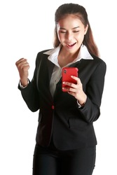 Smiling Asian woman wearing black suit holding hand smartphone to woring and socialmedia showing signs of joy and happiness in white background. Concept happy cheerful and delighted