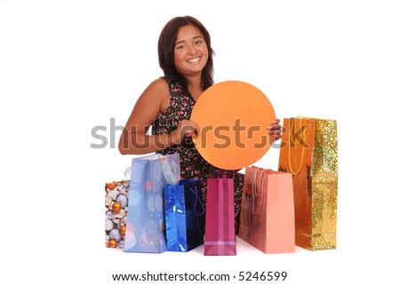 Smiling asian woman with a several bags holding a blank blackboard