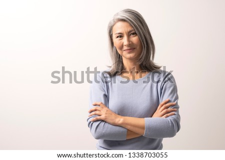 Smiling Asian Woman With Crossed Hands Stands In Front Of White Background. Charming Grey-Haired Woman With Crossed Arms Gently Smiles. Portrait.