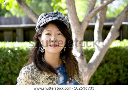 smiling asian woman with herringbone cap