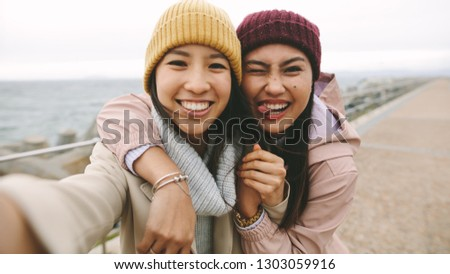 Smiling asian women standing outdoors holding each other on a winter morning. Cheerful asian women in winter wear having fun making faces standing near the sea on a cold morning. Stock fotó ©