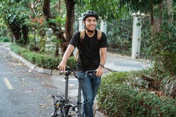 smiling asian young man walking with folding bike on the street