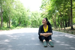 Smiling Asian young woman in sportwear sitting and relaxing with her mind on concrete floor after exercise in the natural light garden.