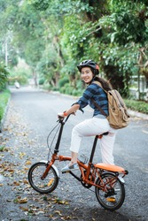 smiling asian young woman wearing helmet and bag ride his folding bike when looking the camera