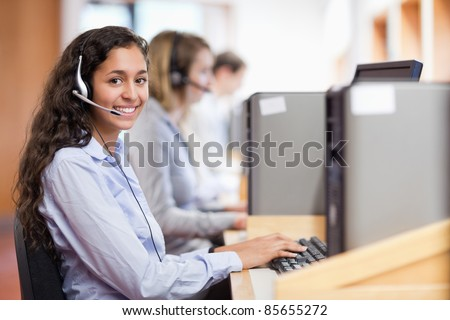 Smiling assistant working with a computer in a call center
