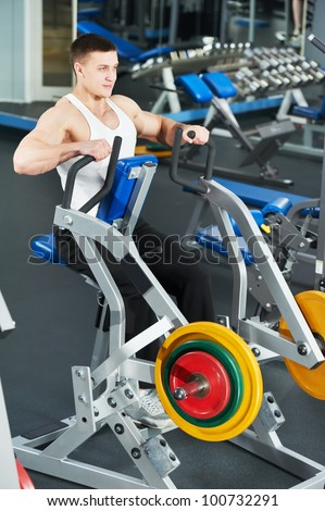 Smiling athlete bodybuilder man doing muscles exercises at weight machine in fitness sport club gym