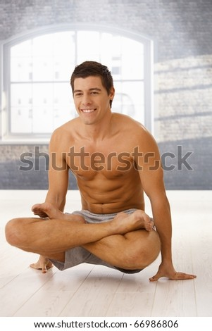 Smiling athletic guy doing yoga exercise in lotus posture in gym.?