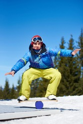 Smiling athletic male snowboarder training, balancing on snowboard on snowy hill on background of blue sky and spruce trees on sunny day. Winter extreme mountain sports, active lifestyle concept.