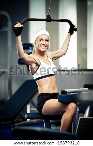 Smiling athletic woman pumping up muscles in a gym