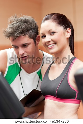 Smiling athletic woman standing on a running machine with her personal coach in a fitness center