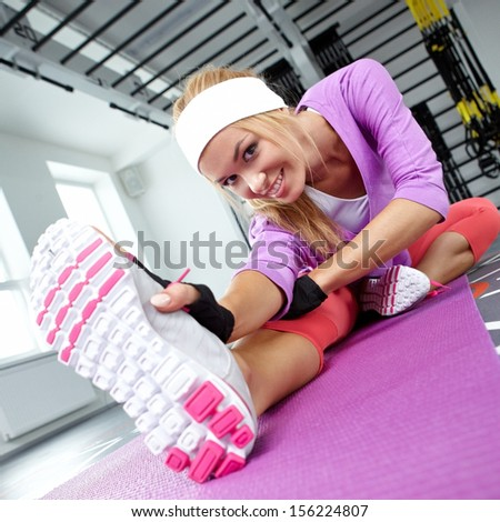 Smiling athletic woman stretches the muscles in a gym
