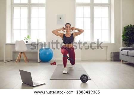 Smiling athletic young woman training legs at home watching active sports workout video lesson. Fit female athlete in activewear doing forward lunges exercise with elastic resistance rubber glute band